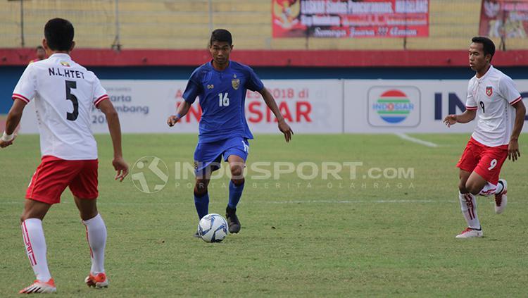Pemain Myanmar berusaha menutup pergerakan pemain Thailand. Copyright: Fitra Herdian/Indosport