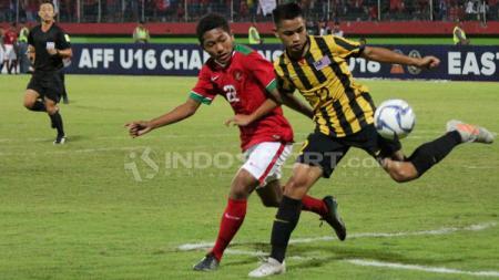 Muhammad Fajar menghalau pemain Malaysia untuk mengambil bola. - INDOSPORT