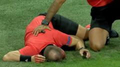 Indosport - Wasit sepakbola tergeletak usai terkena lemparan batu.