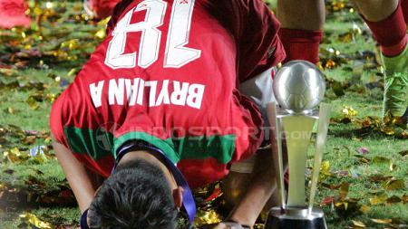 Sujud syukur Brylian bersama dengan Piala AFF U-16 2018 di sampingnya. - INDOSPORT