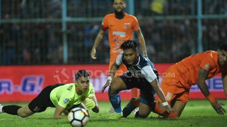 Ahmad Nur Hardianto memandang bola setelah upayanya mencetak gol digagalkan Nadeo Argawinata. - INDOSPORT
