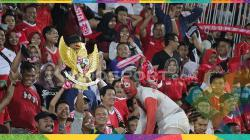 Suporter Indonesia, Andi Kiswantoro, membawa patung Garuda Pancasila.