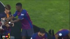 Indosport - Oumane Dembele memberikan trofi Super Copa Spanyol ke pemain lain.