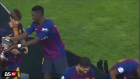 Oumane Dembele memberikan trofi Super Copa Spanyol ke pemain lain. - INDOSPORT