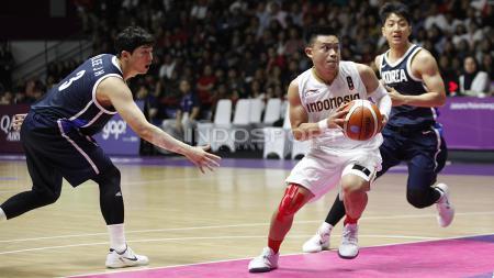 Aksi pebasket Indonesia, Andakara Prastawa (tengah) melewati hadangan dua pemain Korea. - INDOSPORT