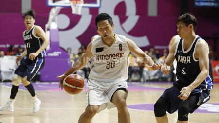 Aksi pebasket Indonesia, Xaverius Prawiro mendrible bola melewati hadangan pemain Korea, Kim Sunhyung (kanan). - INDOSPORT