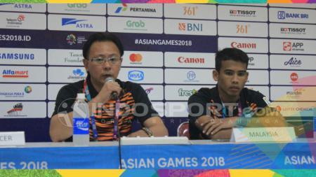 Pelatih Timnas Malaysia, Ong Kim Swee (kiri) ditemani pemainnya Rasid Muhammad Safawi seusai laga kontra Kyrgyztan di Stadion Si Jalak Harupat, Kabupaten Bandung, Rabu (15/08/18). - INDOSPORT