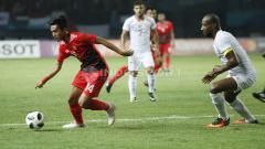 Indosport - Pemain Indonesia U-23, Septian David Maulana berusaha melarikan diri dari kejaran pemain Palestina.