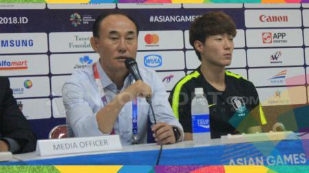 Pelatih Korea, Kim Hag Bum (kiri) ditemai pemainnya Hwang Ui Jo seusai pertandingan menghadapi Bahrain  di Stadion Si Jalak Harupat, Rabu (15/08/18). - INDOSPORT