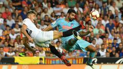 Indosport - Perebutan bola di lini tengah antara pemain Valencia dengan Atletico Madrid.
