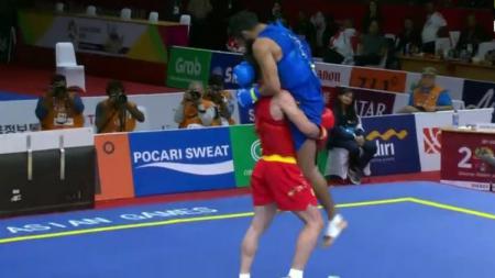 Erfan Ahangarian menggendong Surya Bhanu Partap Singh ke luar arena. - INDOSPORT