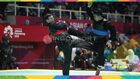 Pesilat Indonesia, Amri Rusdana (sabuk biru) melawan Pesilat Uzbekistan, Nurulla Saidov pada babak 16 besar Kelas F Putra 70kg-75kg di Padepokan Pencak Silat TMII, Rabu (23/08/18). Amri menang 5-0 atas lawannya. - INDOSPORT
