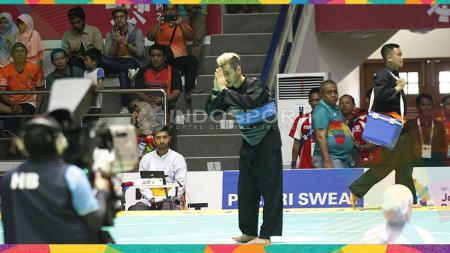 Atlet silat Indonesia, Hanifan Yudani Kusumah (sabuk biru) melawan pesilat Laos, Phoumiphon Vongphakdy (sabuk merah) pada babak perempat final kelas C Putra: 55-60kg di Padepokan Silat TMII, Sabtu (25/08/18). - INDOSPORT