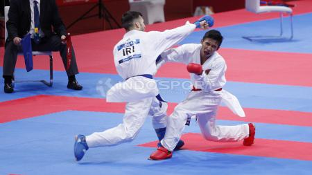 Atlet Karate Indonesia, Rifki Ardian Arrosyid (sabuk merah) melawan atlet Karate Iran, Amir Mahdi Zadeh (sabuk biru) pada babak final Karate kelas Putera -60kg di Plenary Hall JCC, Jakarta, Minggu (26/08/18). Riki menang 9-7 atas lawannya. - INDOSPORT