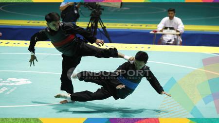 Pesilat Indonesia, Abdul Malik melawan Pesilat Malaysia, Muhammad Faizul M Nasir pada final kelas Putra B 50-55kg  Terkirim dari tablet Samsungdi Padepokan Silat TMII, Senin (27/08/18). - INDOSPORT