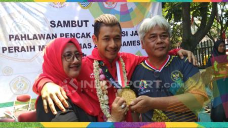 Atlet pencak silat, Hanifan Yudani Kusumah bersama kedua orang tuanya di GOR Pajajaran, Jalan Pajajaran Kota Bandung, Senin (03/09/18). - INDOSPORT