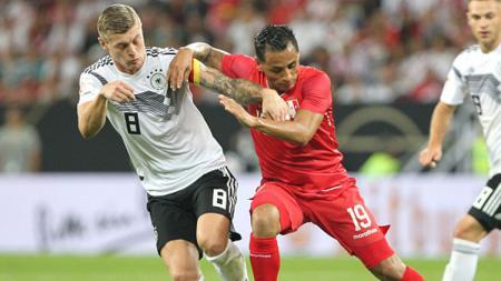 Toni Kroos berduel rebut bola dengan pemain Peru. - INDOSPORT