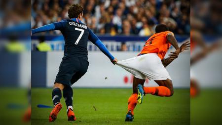 Antoine Griezmann menarik celana Georginio Wijnaldum. - INDOSPORT