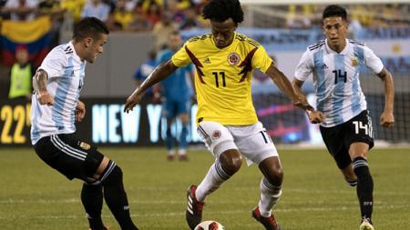 Juan Guillermo Cuadrado dikawal ketat dua pemain Argentina Fabricio Bustos dan Angel Correa. - INDOSPORT