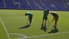 Indosport - Para petugas di Stadion Metalist berhasil memperbaiki kondisi lapangan
