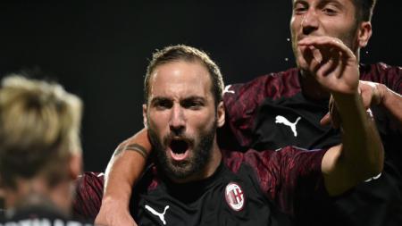 Gonzalo Higuain berselebrasi bersama pemain AC Milan lain usai menetak gol. - INDOSPORT