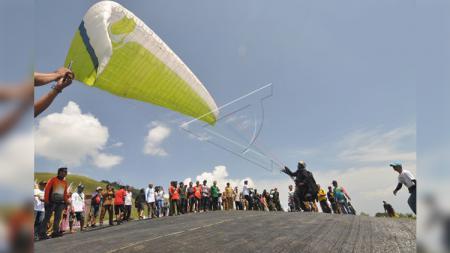 Seorang atlet paralayang mengikuti kejuaraan Indonesia Open Paragliding Palu Nomoni di Arena Paralayang Nomoni Pegunungan Salena di Palu, Sulawesi Tengah, Selasa (25/9). - INDOSPORT