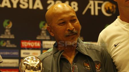 Pelatih Fakhri Husaini dan trofi Piala Asia U-16. - INDOSPORT