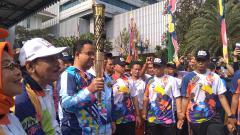 Indosport - Anies Baswedan membawa obor Torch Relay Asian Para Games 2018 Jakarta.