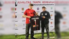 Indosport - Asisten Manajer Persipura, Bento Madubun saat memberikan sebuah Jersey bernomor punggung 1 bernama Haringga Sirila kepada Ketua Umum Jakmania, Ferry Indrasjarief.