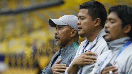 Fakhri Husain dan jajarannya mengheningkan cipta dalam laga perempatfinal Piala Asia U-16. - INDOSPORT