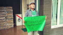 Indosport - Pentolan Bonek, Andie Peci protes di depan kantor PSSI.