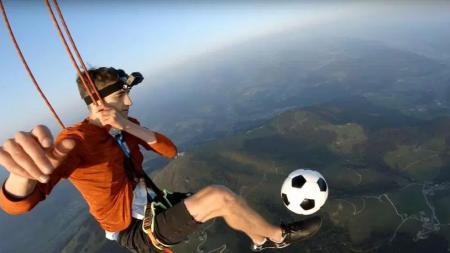 Kieran Brown saat berglantungan dibawah balon udara sambil memainkan bola. - INDOSPORT