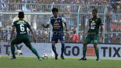 Indosport - Jayus Hariono mencari celah untuk mengalirkan bola diantara hadangan dua gelandang Persebaya.