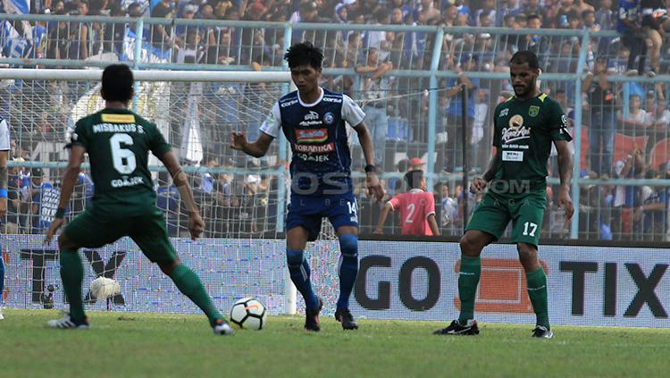 Jayus Hariono mencari celah untuk mengalirkan bola diantara hadangan dua gelandang Persebaya. Copyright: Ian Setiawan/INDOSPORT