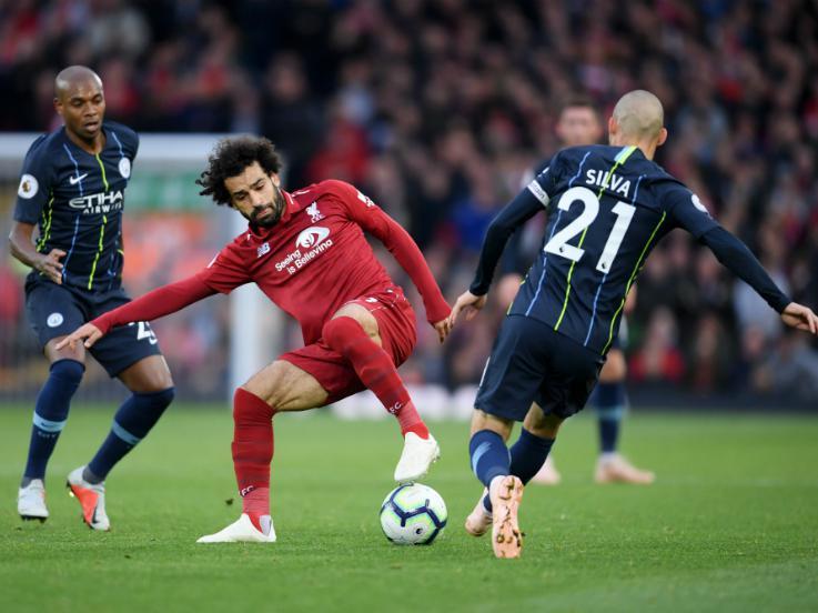 Mohamed Salah tengah berebut bola dengan David Silva. Copyright: Getty Images
