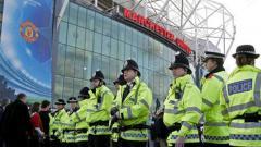Indosport - Polisi berjaga di luar stadion Old Trafford, markas Man United.