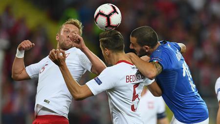 Para pemain Polandia dan Italia berduel di udara dalam laga UEFA Nations League. - INDOSPORT