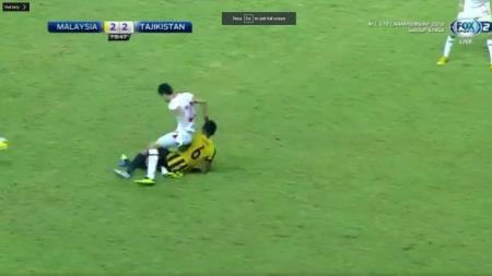 Pemain Malaysia Nabil Hakim saat melakukan tekel ke Khuseyn Nurmatov. - INDOSPORT