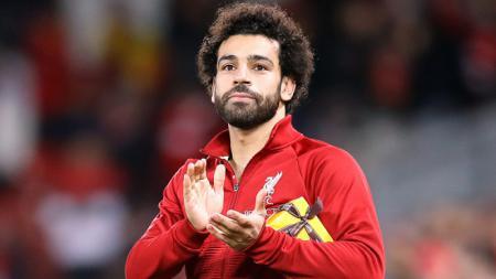 Mohamed Salah pasca menerima hadiah dari tribun fans Liverpool di Liga Champions. - INDOSPORT