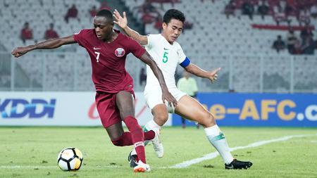 Kapten Timnas Indonesia U-19, Nur Hidayat (kanan) saat berduel dengan pemain Qatar U-19 - INDOSPORT