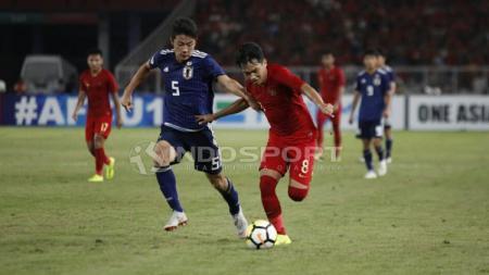 Witan Sulaeman berusaha menganmakan bola dari pemain Jepang - INDOSPORT