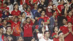 Indosport - Suporter Timnas Indonesia menunjukkan raut kekecewaan usai Skuat Garuda Nusantara kalah 2-0 dari Jepang U-19.