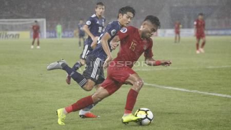 Saddil Ramdani berebut bola dengan pemain Jepang. - INDOSPORT