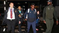 Indosport - Pogba saat tiba di bandara Manchester tanpa rekan-rekannya.