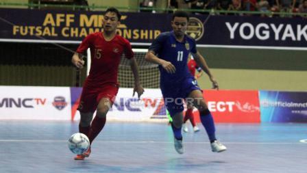 Rio Pangestu (kiri) membawa bola di jaga ketat oleh pemain Thailand.