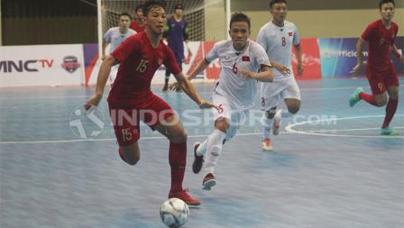 Pemain Indonesia, Rio Pangestu Putra, beradu kecepatan dengan pemain Vietnam, Pam Duc Hoa.