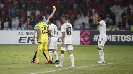 Wasit memberikan kartu kuning kepada pemain Timor Leste yang melakukan pelanggaran. - INDOSPORT
