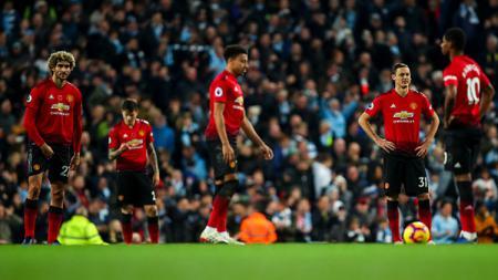 Para pemain Manchester United tertunduk lesu usai dihempaskan oleh Manchester City pada akhir pekan kemarin. - INDOSPORT