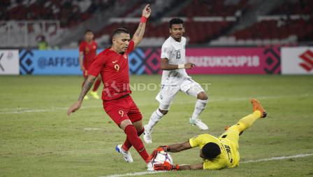 Striker Timnas Indonesia, Alberto Goncalves mencoba melewati kiper Timor Leste, Fagio Augusto (kanan).