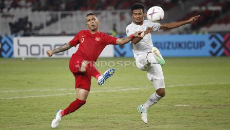 Aksi Alberto Goncalves menendang bola ke arah gawang Timor Leste diganggu pemain belakang Timor Leste.